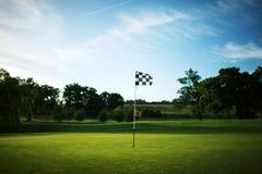 Bandera a cuadros en un verde del campo de golf con un cielo azul fotografía de archivo