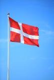 Bandera danesa con el cielo azul en fondo imagen de archivo