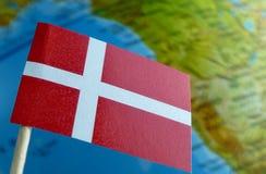 Bandera danesa con un mapa del globo como fondo imagen de archivo