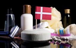 Bandera danesa en el jabón con todos los productos para la gente Fotos de archivo