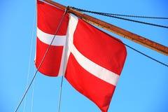 Bandera danesa en fondo del cielo azul de la nave imágenes de archivo libres de regalías