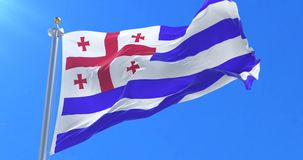Bandera de Adjaran que agita en el viento en lento con el cielo azul, lazo