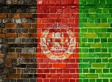 Bandera de Afganistán en un fondo de la pared de ladrillo Fotos de archivo