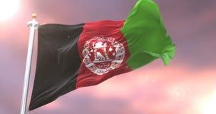 Bandera de Afganistán que agita en el viento en lento en la puesta del sol, lazo stock de ilustración