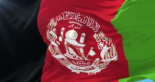 Bandera de Afghanistani que agita en el viento en lento con el cielo azul, lazo