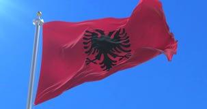Bandera de Albania que agita en el viento con el cielo azul, lazo