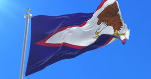 Bandera de American Samoa que agita en el viento en lento con el cielo azul, lazo
