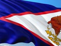Bandera de American Samoa que agitan en el viento contra el cielo azul profundo Tela de alta calidad imagen de archivo libre de regalías