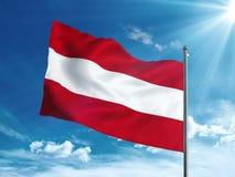 Bandera de Austria que agita en el cielo azul Foto de archivo