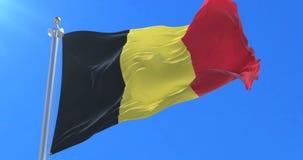 Bandera de Bélgica que agita en el viento en lento con el cielo azul, lazo