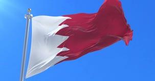 Bandera de Bahrein que agita en el viento en lento con el cielo azul, lazo