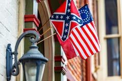 Bandera de batalla confederada y bandera americana atada al edificio, centro de la ciudad histórico de la guerra civil de 34 estr fotografía de archivo