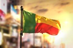 Bandera de Benin contra fondo borroso ciudad en el contraluz de la salida del sol Foto de archivo