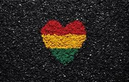 Bandera de Bolivia, bandera boliviana, corazón en el fondo negro, piedras, grava y tabla, papel pintado foto de archivo libre de regalías
