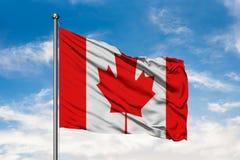 Bandera de Canadá que agita en el viento contra el cielo azul nublado blanco Indicador canadiense fotografía de archivo libre de regalías