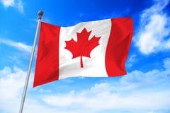 Bandera de Canadá que se convierte contra un cielo azul Foto de archivo libre de regalías