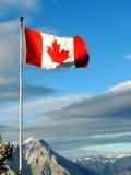 Bandera de Candian en un pico en las montañas rocosas Imagen de archivo