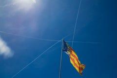 Bandera de Cataluña en Valencia, España en el fondo del cielo azul Fotos de archivo