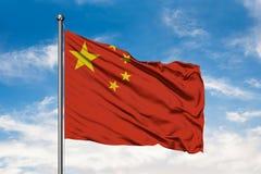 Bandera de China que agita en el viento contra el cielo azul nublado blanco Indicador chino foto de archivo