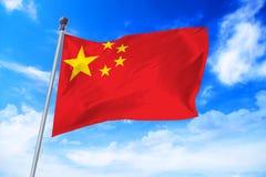 Bandera de China que se convierte contra un cielo azul Imágenes de archivo libres de regalías