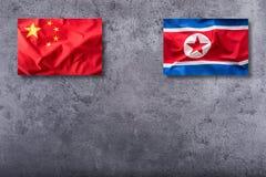 Bandera de China y de Corea del Norte en fondo concreto imágenes de archivo libres de regalías