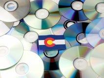 Bandera de Colorado encima de la pila del CD y del DVD aislada en blanco imagenes de archivo