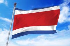 Bandera de Costa Rica que se convierte contra un cielo azul imagen de archivo