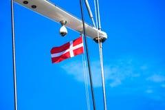 Bandera de Dinamarca en el palo de la nave, cielo azul en fondo foto de archivo