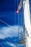 Bandera de Dinamarca en el palo de la nave, cielo azul en fondo imagen de archivo libre de regalías