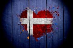 Bandera de Dinamarca en la forma del corazón en un fondo oscuro imagen de archivo libre de regalías
