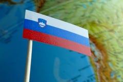 Bandera de Eslovenia con un mapa del globo como fondo Imágenes de archivo libres de regalías