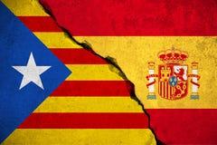 Bandera de España en la pared de ladrillo quebrada y media bandera catalan, referéndum del voto para el separatismo nacional de l Imagen de archivo libre de regalías