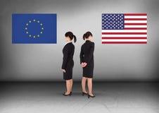 Bandera de Europa o bandera de América con la empresaria que mira en direcciones opuestas Fotografía de archivo