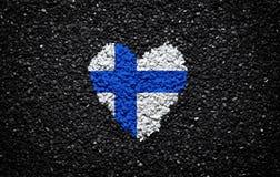 Bandera de Finlandia, bandera finlandesa, corazón en el fondo negro, piedras, grava y tabla, papel pintado texturizado fotos de archivo