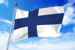 Bandera de Finlandia que se convierte contra un cielo azul claro Foto de archivo libre de regalías