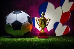 Bandera de Francia, campeón de oro \ 'taza de s y balón de fútbol en hierba Deporte del concepto Foto de archivo