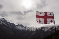 Bandera de Georgia contra los tops blancos de las montañas de piedra Fotos de archivo libres de regalías