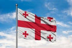 Bandera de Georgia que agita en el viento contra el cielo azul nublado blanco Indicador georgiano foto de archivo libre de regalías