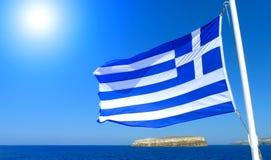 Bandera de Grecia con el cielo azul y mar y el sol imagen de archivo libre de regalías