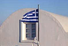 Bandera de Grecia en luz de la puesta del sol en Oia, isla de Santorini Fotos de archivo