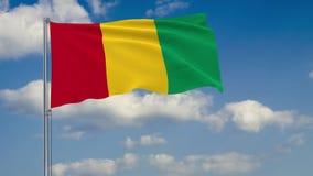 Bandera de Guinea contra el fondo del cielo de las nubes ilustración del vector