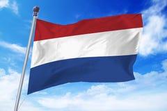 Bandera de Holanda que se convierte contra un cielo azul claro Imágenes de archivo libres de regalías