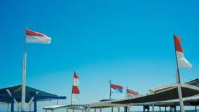 Bandera de Indonesia en el barco del transporation en el mar con el cielo azul y la onda imagenes de archivo