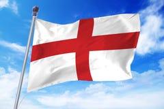 Bandera de Inglaterra que se convierte contra un cielo azul claro Foto de archivo libre de regalías