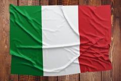 Bandera de Italia en un fondo de madera de la tabla Opini?n superior arrugada de la bandera italiana imagen de archivo
