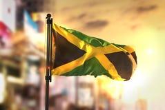 Bandera de Jamaica contra fondo borroso ciudad en la salida del sol Backligh Fotos de archivo libres de regalías