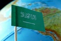 Bandera de la Arabia Saudita con un mapa del globo como fondo Imagenes de archivo