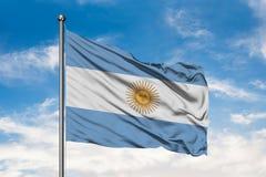 Bandera de la Argentina que agita en el viento contra el cielo azul nublado blanco Indicador argentino ilustración del vector