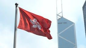 Bandera de la cámara lenta de Hong Kong que agita en el viento con la torre del Banco de China metrajes