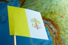 Bandera de la Ciudad del Vaticano con un mapa del globo como fondo Imagen de archivo libre de regalías